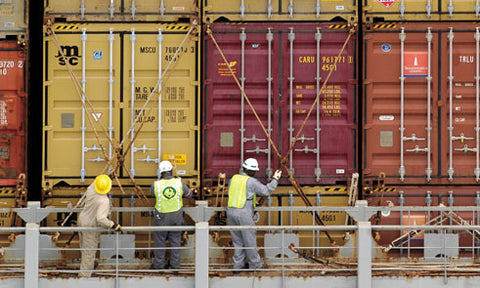 Workers lashing shipping containers with rods