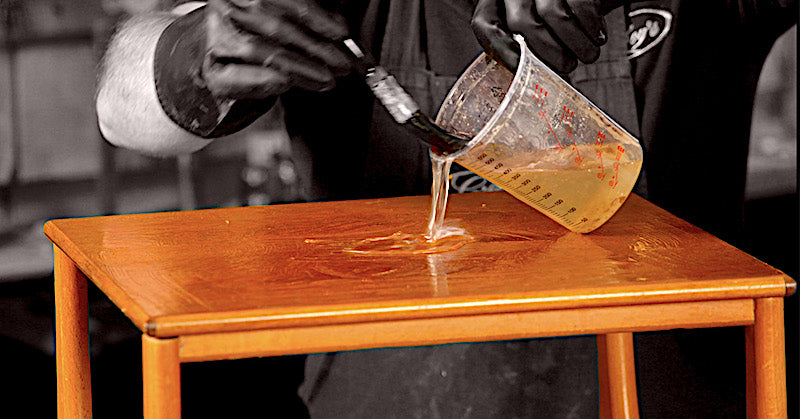 pouring the stripper on the surface of the Nathan teak table