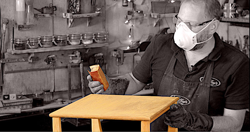 sanding the stripped surface of the teak table