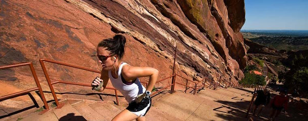 woman running red rocks stairs