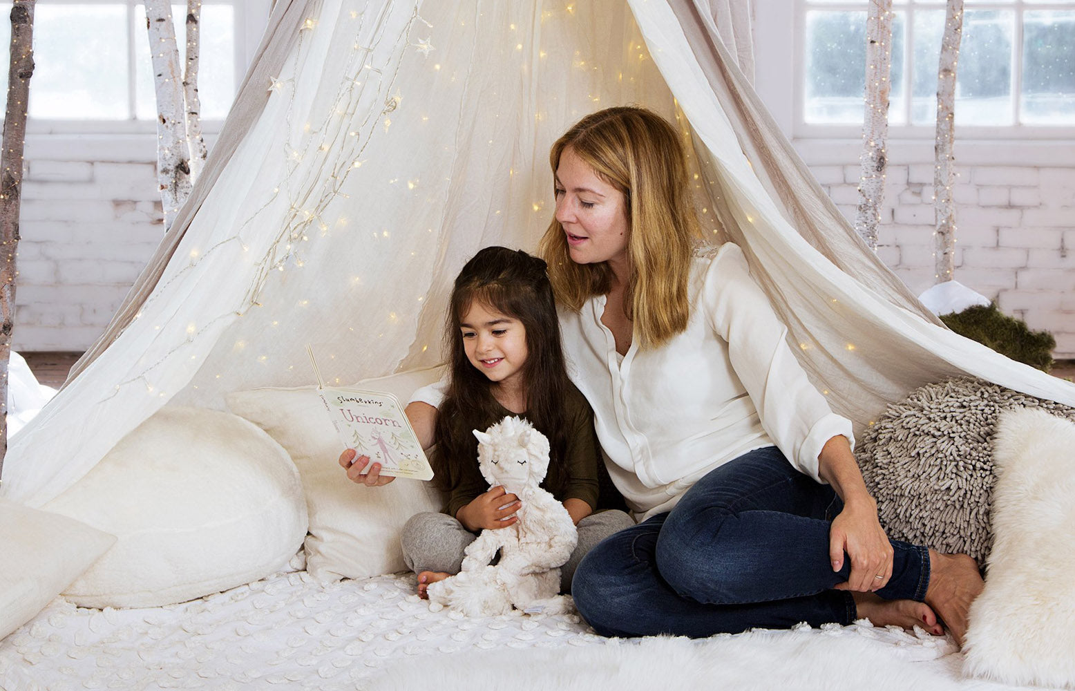 Mom and daughter reading a book in a winter wonderland