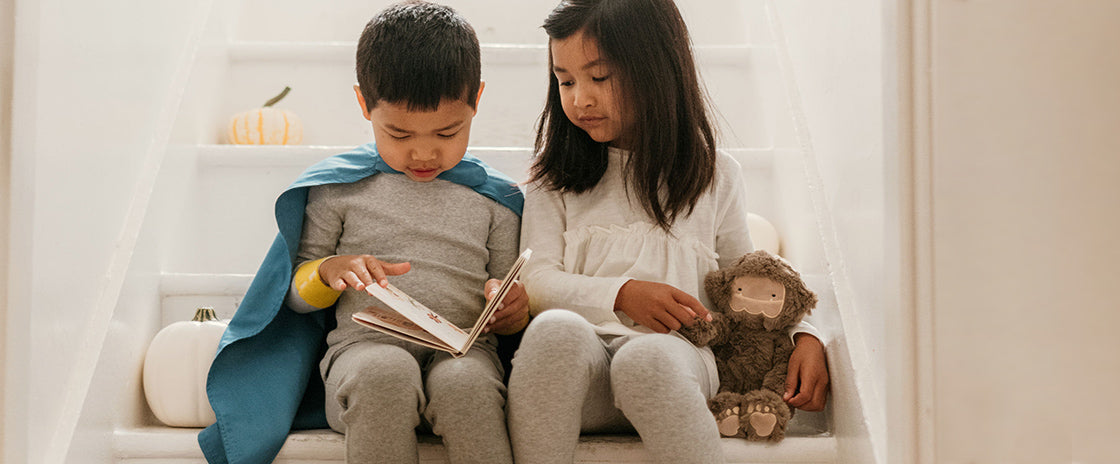 Brother and sister reading the bigfoot book with bigfoot kin