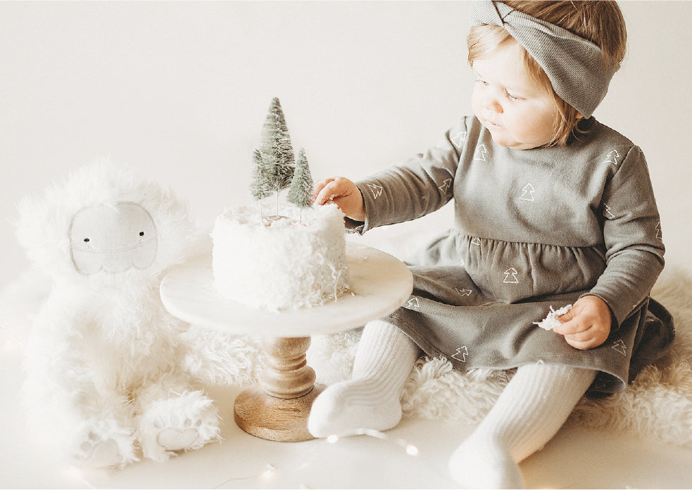 Little girl with yeti stuffie eater her birthday cake