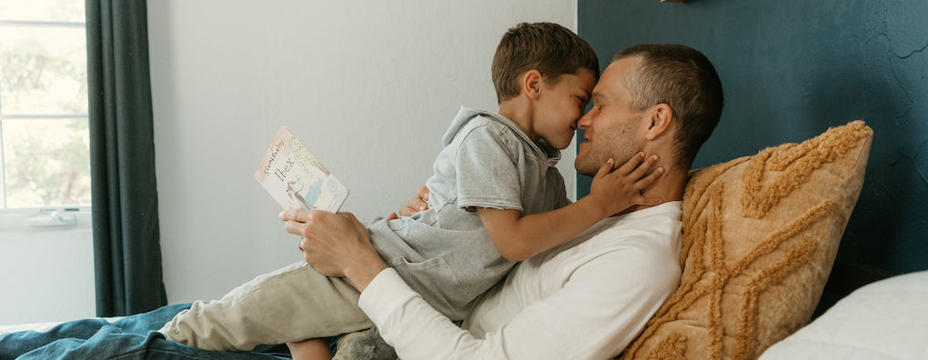 Boy and father reading ibex and embracing
