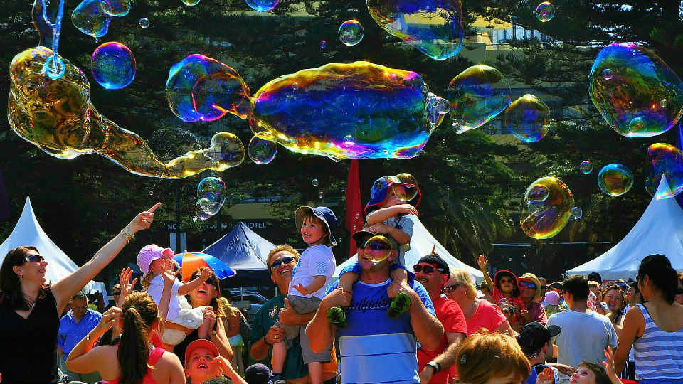 Our bubble performer entertains a family at a festival with monster giant bubbles