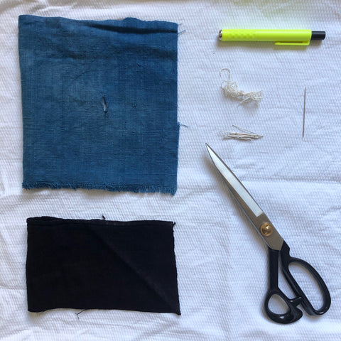Material with hole in, patch to cover hole, chalk, thread, pins, needle and scissors