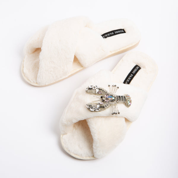 Bobbi Parka fluffy faux fur slippers in cream with a crystal lobster brooch