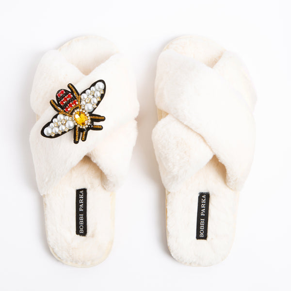 Bobbi Parka fluffy faux fur slippers in cream with a crystal bee brooch