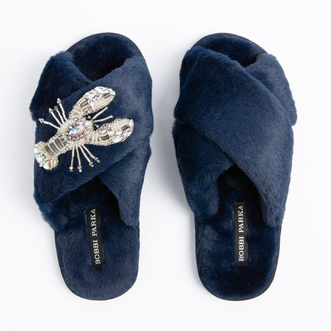 Bobbi Parka fluffy faux fur slippers in navy with a crystal lobster brooch