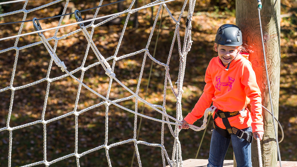 young girl on ropes course with braided, spliced lobster claw