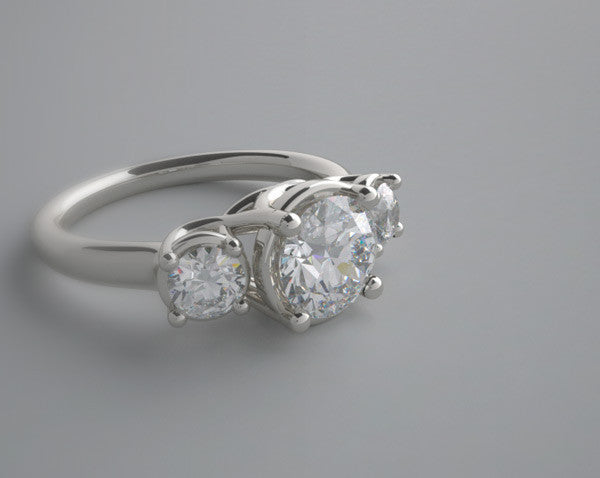 Platinum three diamond engagement ring setting for a round gemstone