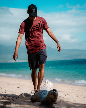Iesū (Jesus) Tee in heather cardinal at the beach