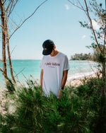 E Pule Kākou (Let Us Pray) tee White with Red Text at the Beach