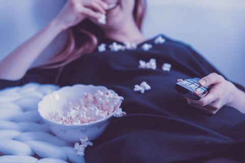 girl eating popcorn with remote in hand