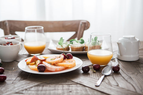 fruit on a plate on a wooden table with two glasses of juice