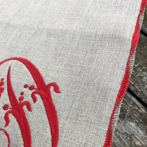 Natural flax linen serviette with Christmas red embroidered french monogram and decorative scalloped stitched edging