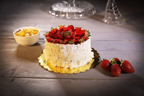 white chocolate cake topped with strawberries