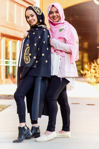 two muslim friends wearing embroidered hijabs in black and gold, and rose and white