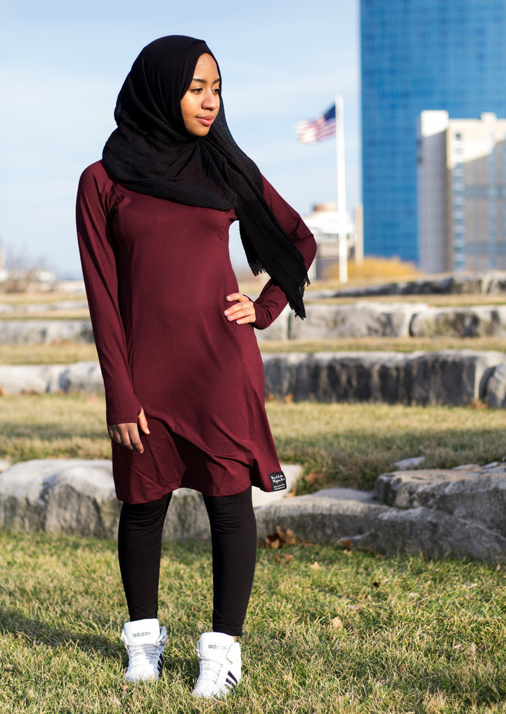 black muslim woman outside in maroon and black modest workout apparel
