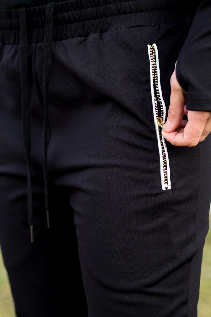woman closing the zipper of a pocket on black jogger pants