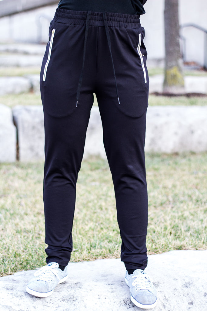 a woman wearing black jogger pants with gold zippers and drawstring