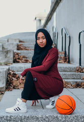 black muslim woman in maroon and black modest workout apparel with a basketball