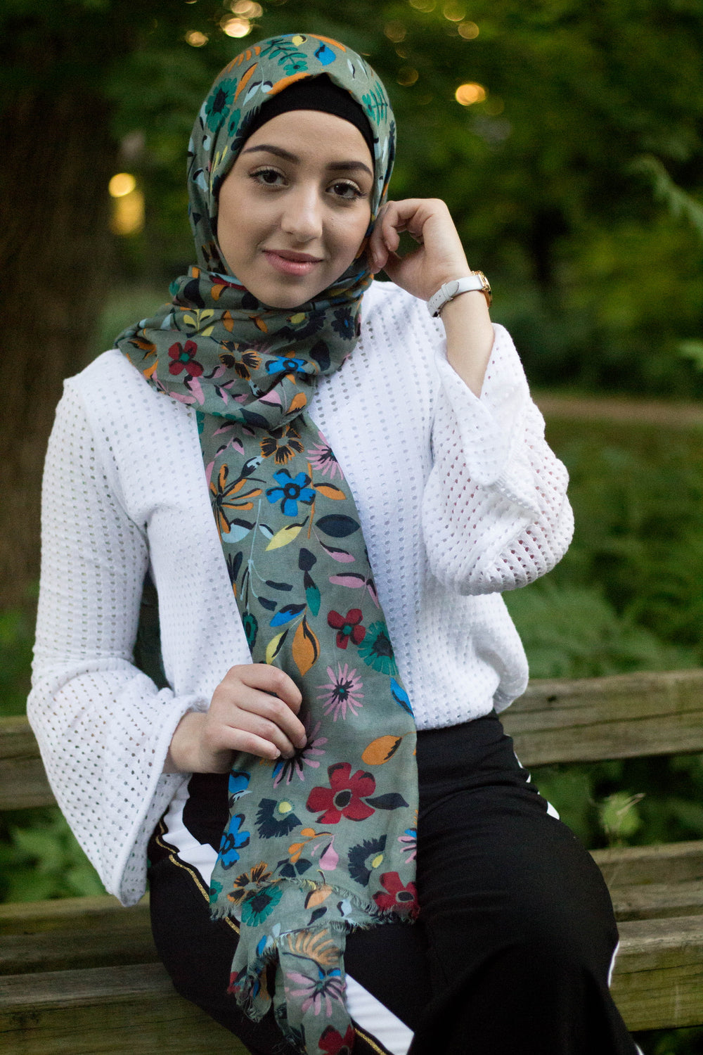 muslim woman wearing a green hijab with floral prints in multiple colors: yellow, red, blue, green,orange, and pink