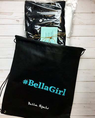 a black drawstring duster bag labeled #bellagirl with workout apparel inside