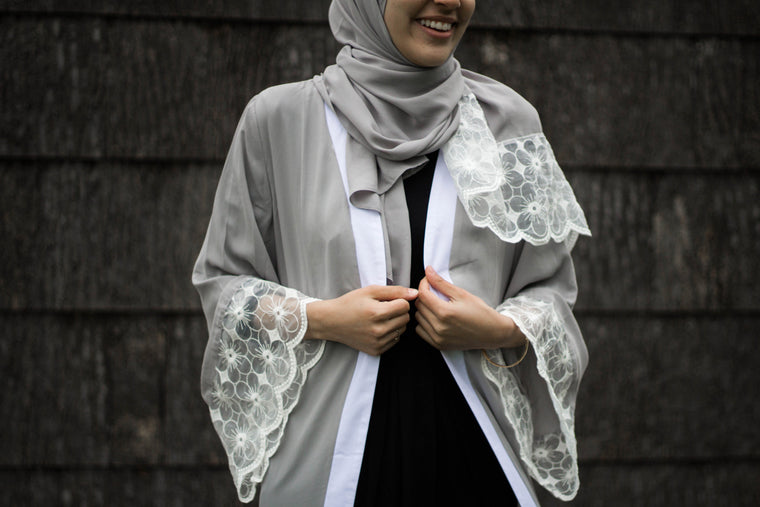 woman wearing an abaya in silver embellished with lace sleeves and a matching hijab