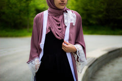 woman wearing an abaya in mauve embellished with lace sleeves and a matching hijab