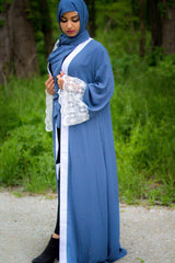 woman wearing an abaya in blue embellished with lace sleeves and a matching hijab