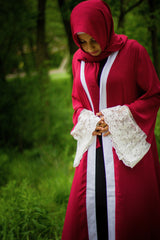 woman wearing an abaya in red embellished with lace sleeves and a matching hijab