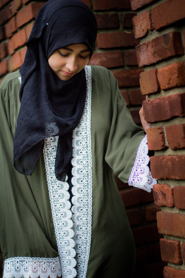 woman wearing an abaya in olive green embellished with white lace sleeves