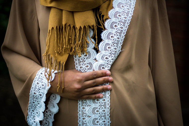 woman wearing an abaya in tan embellished with white lace sleeves