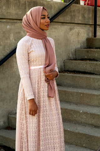 black muslim woman wearing a long sleeve maxi dress in pink lace with a satin waist tie and mauve hijab