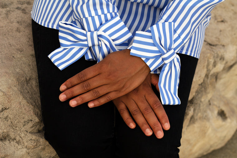 large bow on striped sleeves of a white and blue blouse