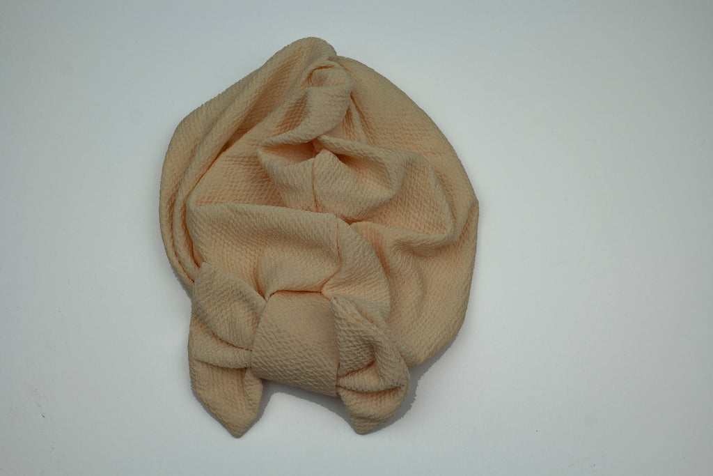 creme slip on turban with a large bow on the front