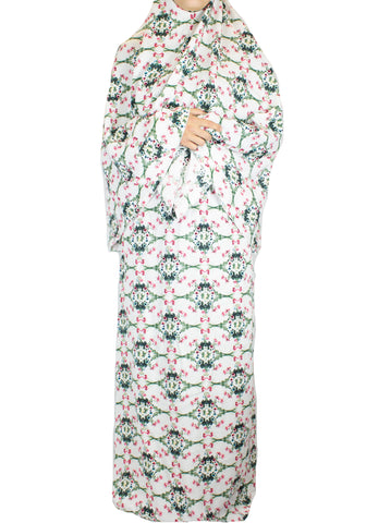 two piece salah outfit with hijab and skirt printed with pink, green, and white floral