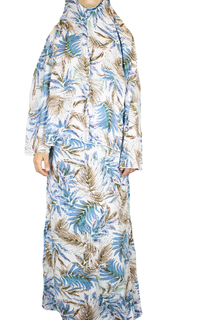 two piece salah outfit with hijab and skirt printed with blue, white, and beige leaves