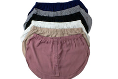 bundle of fake shirt extenders in navy mauve silver black tan and white with buttons and an elastic waistband