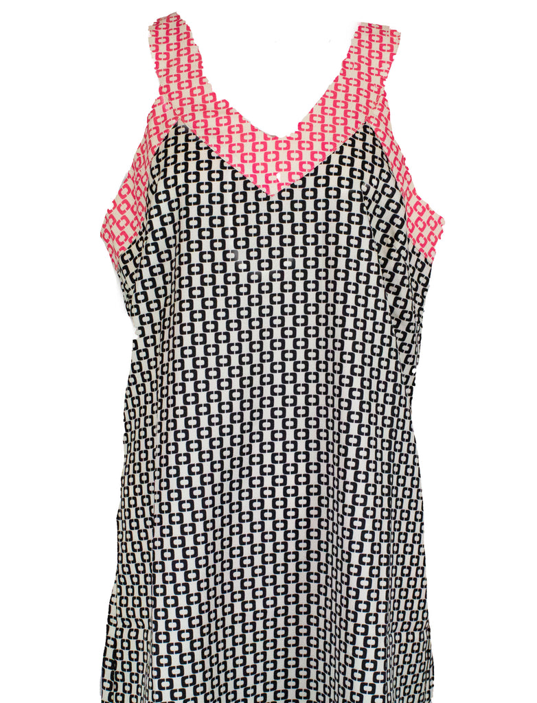 Sleeveless long top that comes to the mid-thigh. Geometric print in white, black, and pink.