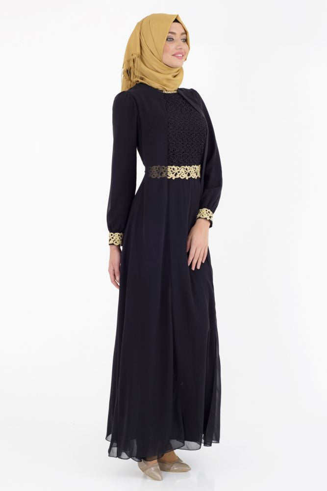 turkish woman wearing a gold hijab an elegant black long sleeve maxi dress with gold embellishments