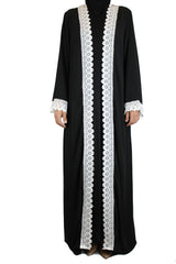 woman wearing an abaya in black embellished with white lace sleeves