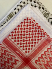 red, black, and white shemagh stacked on top of each other in a bundle
