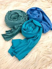 teal, turquoise, and periwinkle jersey hijabs laid out on fur rug