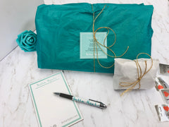 a flatlay of gift wrapped products in teal and white tissue paper