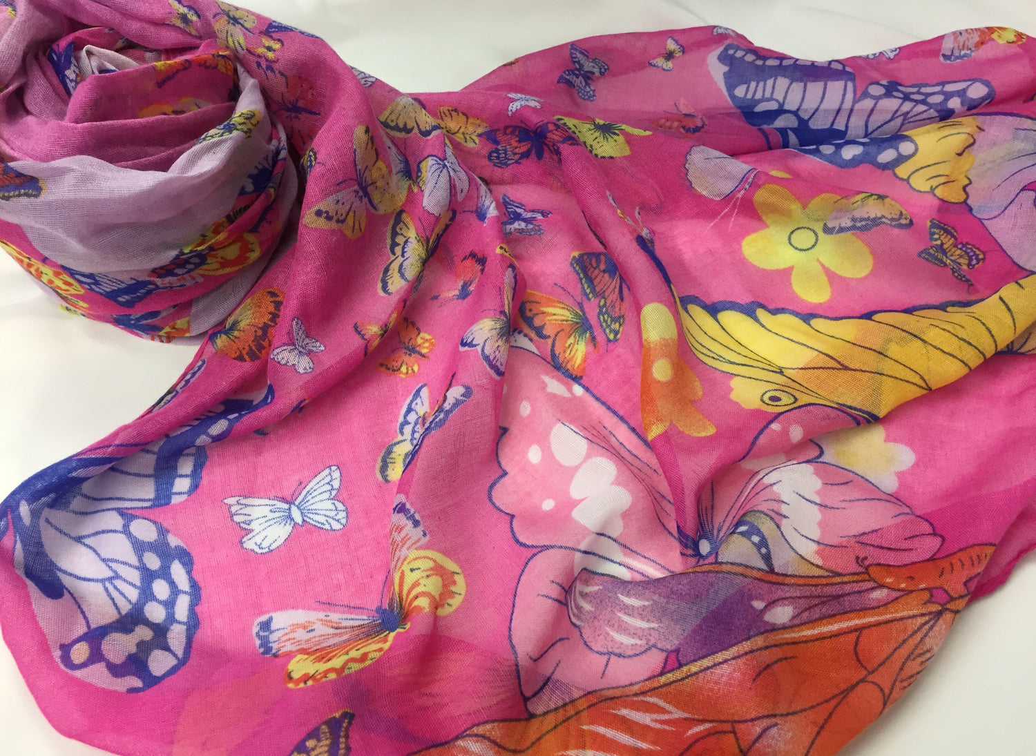 soft pink hijab printed with butterflies in green, pink, red, yellow, purple, and blue
