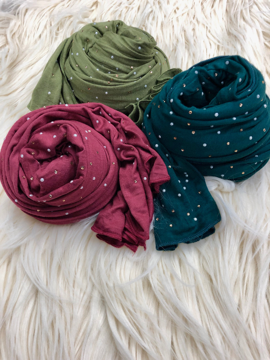 three jersey hijabs embellished with beaded pearls in maroon, olive, and forest green laid out on a fur rug