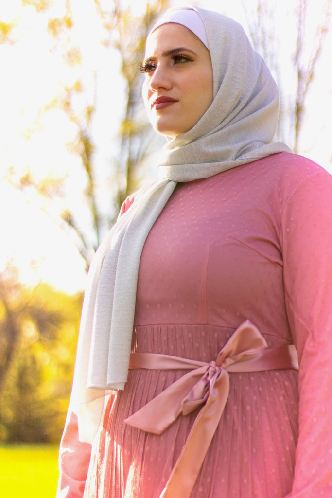 muslim woman wearing silver shimmer jersey hijab and a pink long sleeve maxi dress with polka dots and satin waist belt