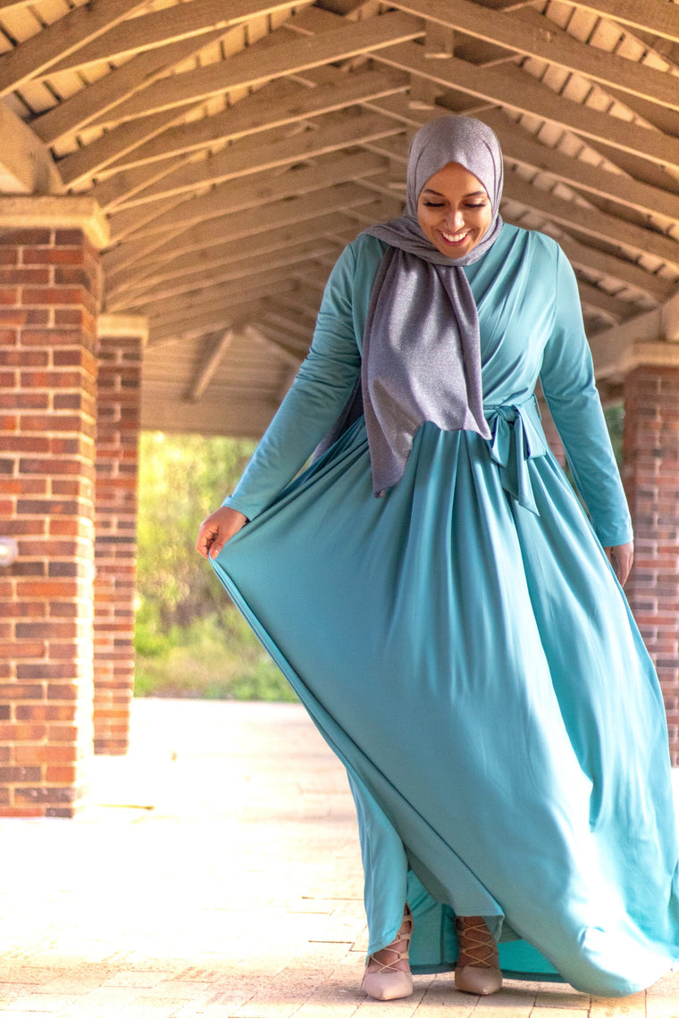 muslim woman wearing a gray shimmer jersey hijab and teal criss cross maxi long sleeve dress with pockets and a waist tie